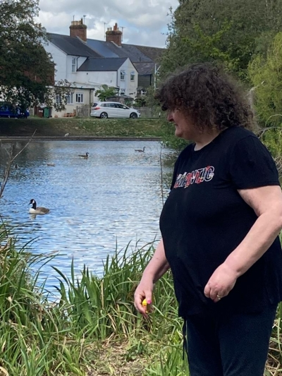 Service user enjoys feeding the ducks on a trip out to the park. Coast Community Care, Bexhill, East Sussex,
