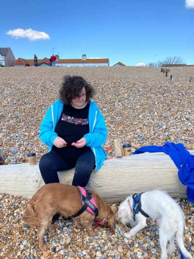 Service user enjoys a trip to the beach with her carer dogs. Coast Community Care, Bexhill East Sussex